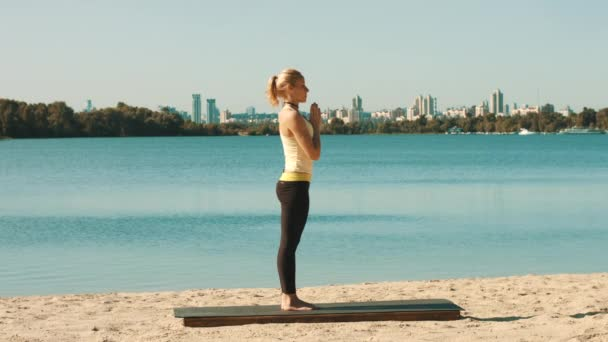 Young woman is doing professional yoga workout on the beach.