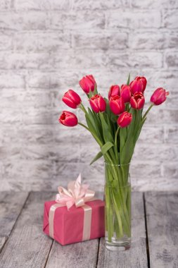 Pink tulips and gift with white bow on gray wooden background. Pink tulips in a glass vase and a gift on a gray white wooden background. stock vector