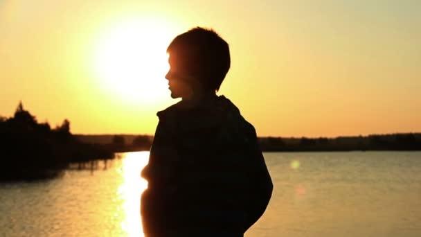 Chlapec, házet kameny do řeky při západu slunce