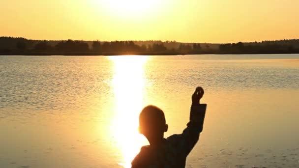 Chlapec, házet kameny do řeky v záři slunce západu slunce, silueta, na vodě
