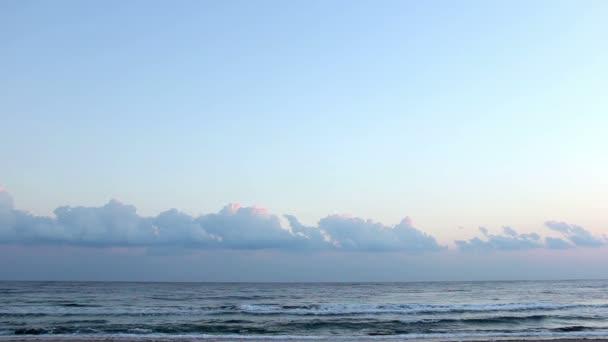 Člověk je spuštěn po pláži za svítání
