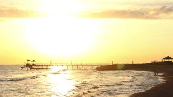 Pár objímání a líbání na pláži při západu slunce