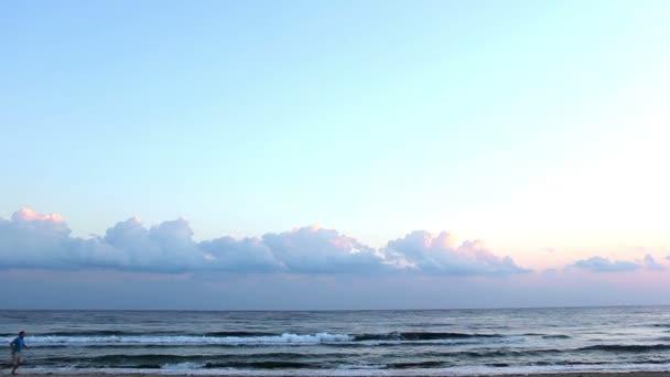 Muž Irunning podél pláže za svítání