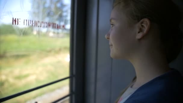 Girl rides on the train looking out the window smiling, slow motion