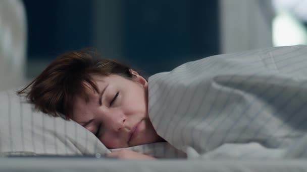 barna nő alszik az ágyon otthon éjjel, mozgó kamera