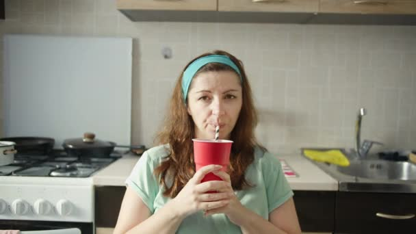 woman sitting in the kitchen at home and drinking soda from a red glass and looking at the camera