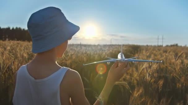 vicces fiú kék kalapban játszik repülőgép az arany búza mező naplementekor, fiú álma, hogy pilóta