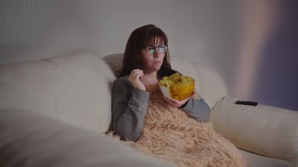 boldog barna nő néz TV-t este eszik chipset és mosolyog