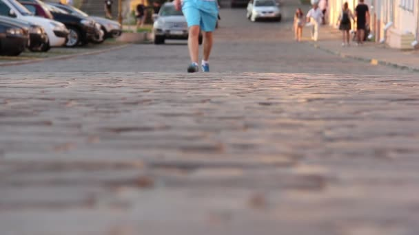 Man walking along the road, close-up shoes goes, sneakers