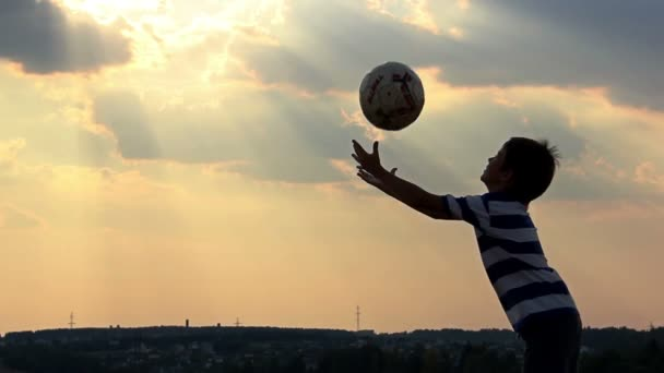 boy dreams of becoming a soccer player, boy playing with a ball at sunset