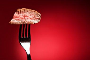 Piece of grilled steak on fork