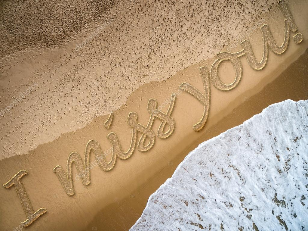 I Miss You written on the beach