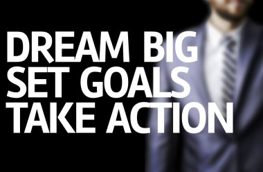 Dream Big Set Goals Take Action written on a board