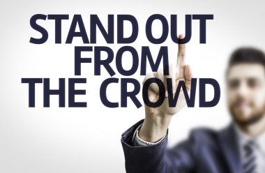 Business man pointing the text: Stand Out From The Crowd