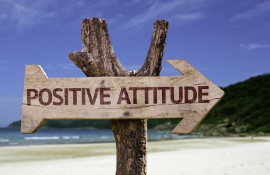 Positive Attitude wooden sign with a beach on background