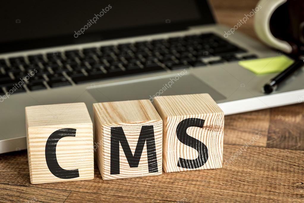 cms written on a wooden cubes