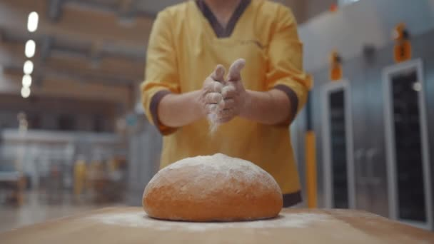 The baker sprinkles flour on the freshly baked bread. Automated bread production.