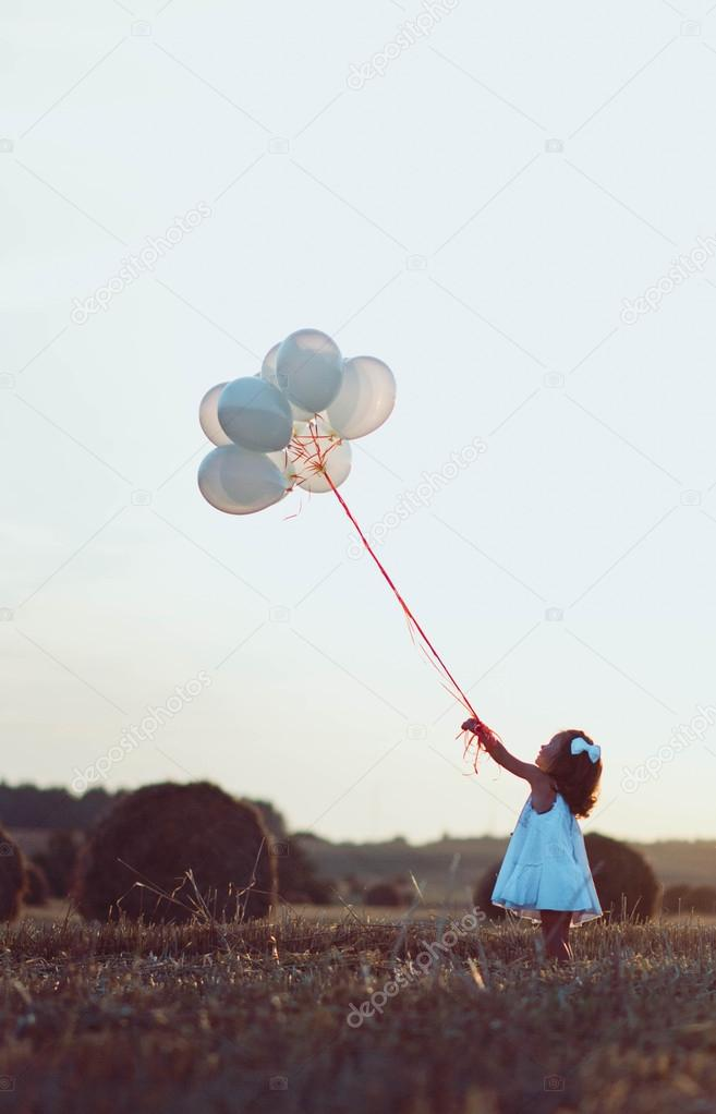 Little girl in the field holding a couple of baloons balloon in sunset light in the summertime
