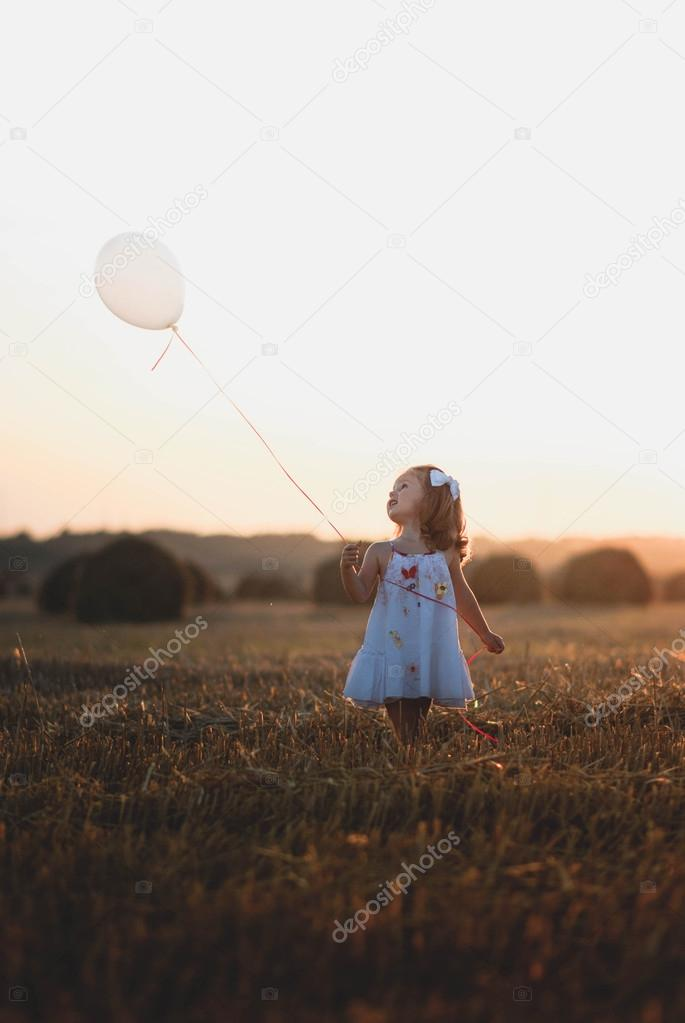 Little girl in the field holding a balloon in sunset light in the summertime