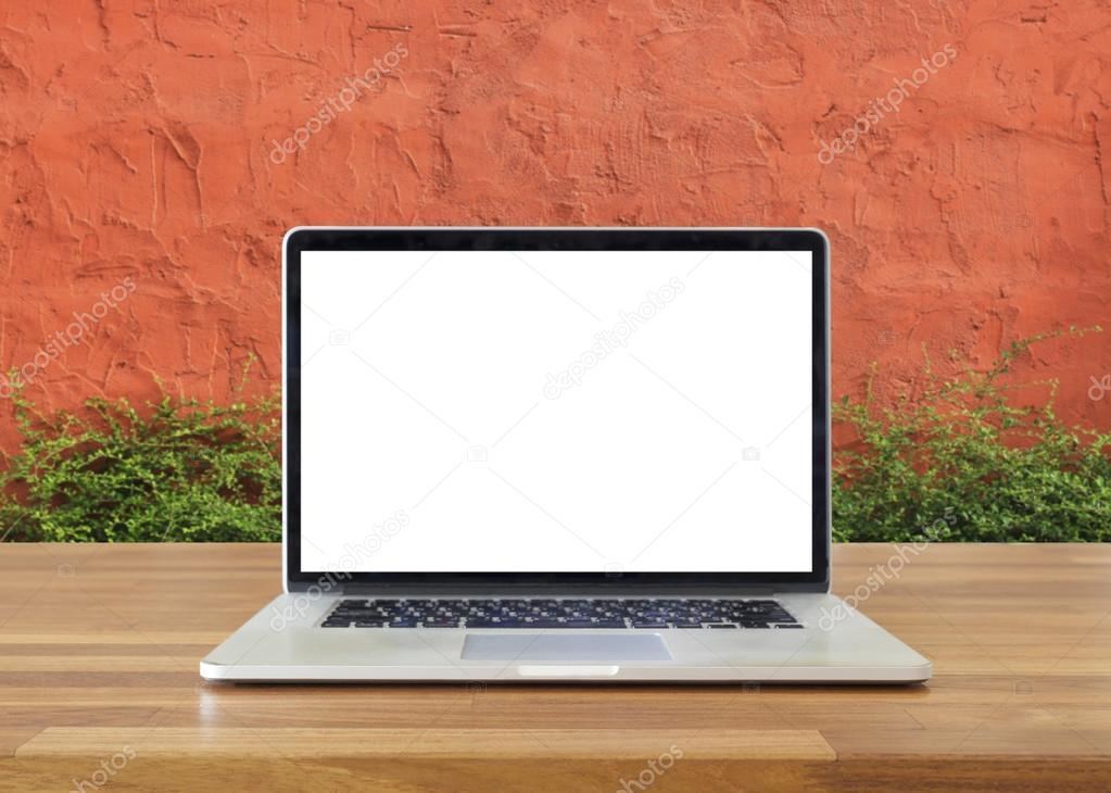 Laptop on table, on  cement  and  tree wall background