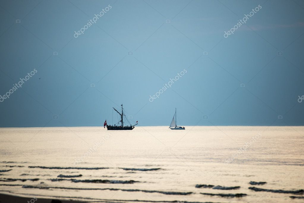 sea with waves and boats before sunset