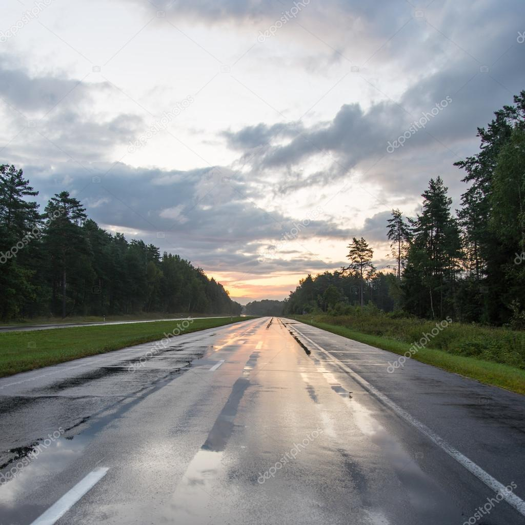 wet asphalt road with sun reflections