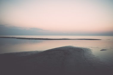 beach after the sunset with sand and clouds - retro, vintage