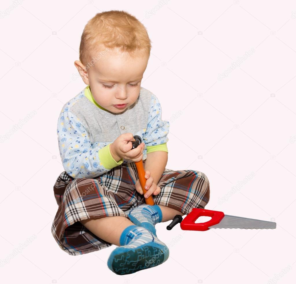 The little boy plays with plastic instrumentamizh a hammer and a