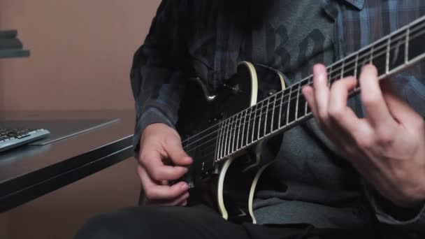 Close up of male hand playing electric guitar.