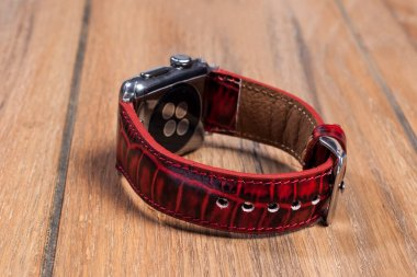 Red leather strap attached to the smart watch on a wooden floor.