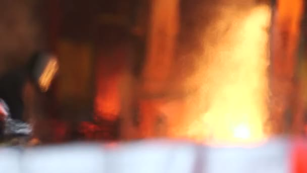 Worker cuts fiery steel blocks