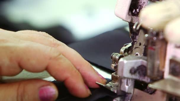 Female hands sews on sewing machine