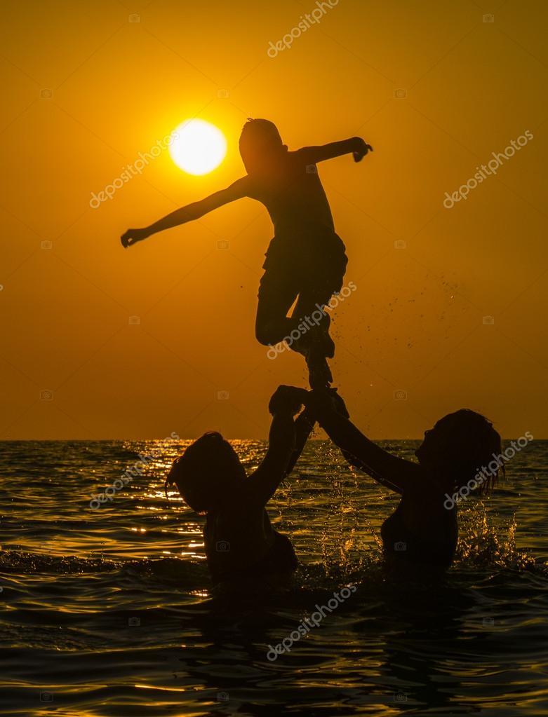 Group of people swimming in sea water at sunset