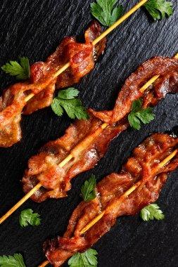 Crispy bacon skewers on a black background
