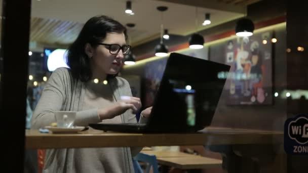 Pracuje s počítači v pěkné Cafe, ona sedí u stolu v okno brýle.