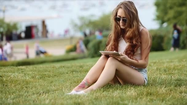 Cute Girl in White Shirt and Jean Shorts in Sitting on the Grass With Her Device and People, Lake and Tall Buildings in the Background