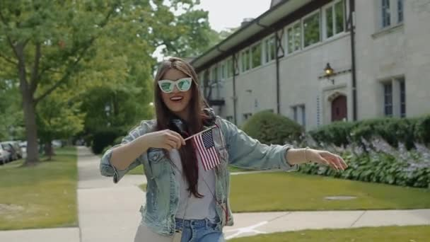 Young Woman in Glasses Waving Stars and Stripes Flag in Front of a Two-Storey House in Neighborhood.