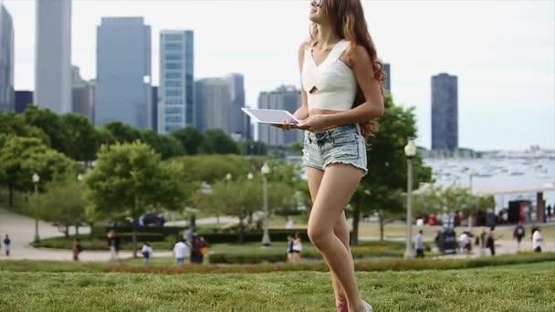 Csinos lány kaukázusi fehér ing és rövidnadrág Jean játszani az eszköz a magas épületek, a tóra és a fák, a háttérben a lassú mozgás