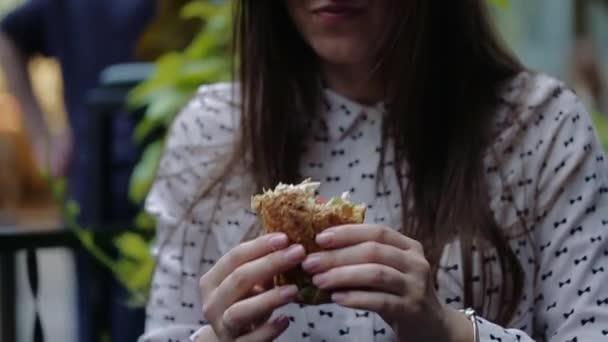 schönes Mädchen isst Burger auf der Straße in Chicago