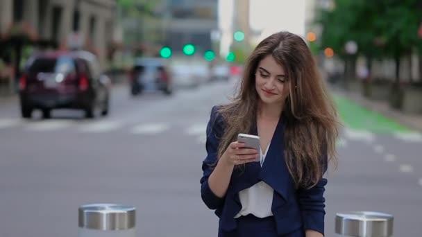 Dívka v modrém bunda stojí u silnice a mluvil po telefonu. S úsměvem