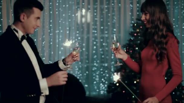 Muž a žena přibližují se sklenkami šampaňského a Bengálsko světel, usmívající se a šťastný