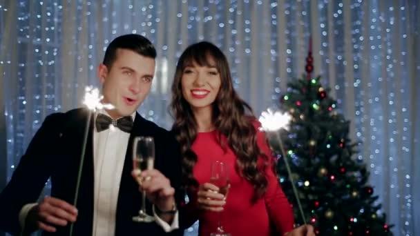 ein kleiner Junge und ein Mädchen heben Gläser Champagner und Wunderkerzen halten
