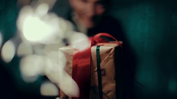 Box s dárky zabalené s červenou stužkou v rukou malého chlapce.