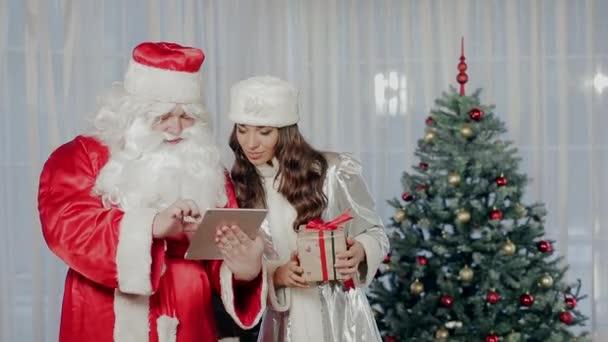 Santa Claus s tabletem Sněhurka s dárkem v ruce stojí poblíž vánoční strom a raduj se