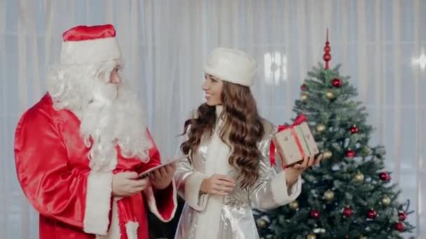 Santa Claus a Sněhurka stojící vedle vánoční stromek, Show navzájem dárky a komunikovat