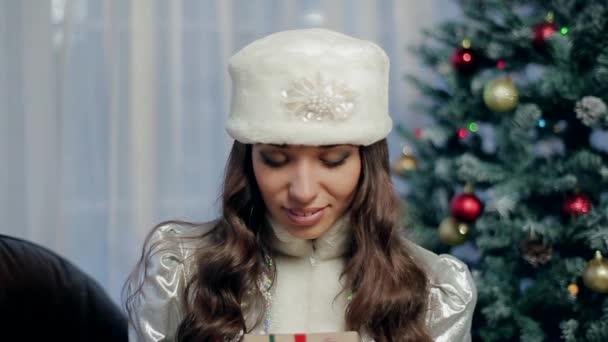 Mladá dívka vybere a rozšiřuje dárek, zabalené s červenou stužkou s velkou mašlí
