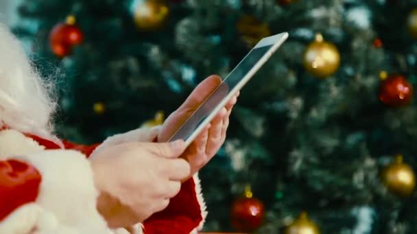 Santa Claus v červené barvy drží Tablet a hází se jeho ruce na jeho práci