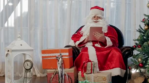 Santa Claus in a Chair Near a Christmas Tree Holding a Tablet. Actively Speaks and Shows the Knee.