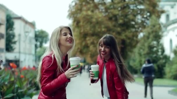 two girls walking on the street with coffee