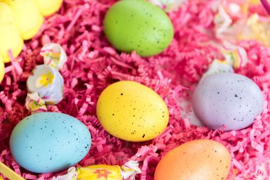 Easter basket with colored eggs, yellow chicks and candy